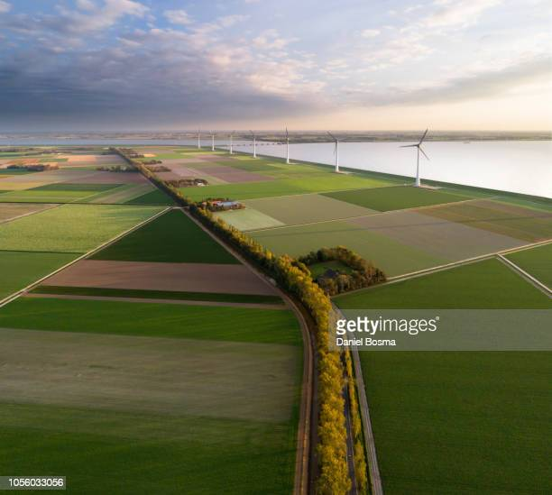 aerial view of a man-made landscape in the netherlands with farms, wind turbines, water and polders. - flevoland stockfoto's en -beelden