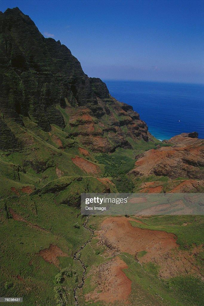 Aerial view of a mountainous cliff bordering the ocean, Kauai, Hawaii : Stock Photo