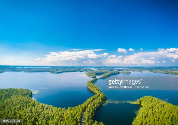 Aerial view of a narrow stretch of land crossing a lake in Punkaharju, Finland on a sunny summer day