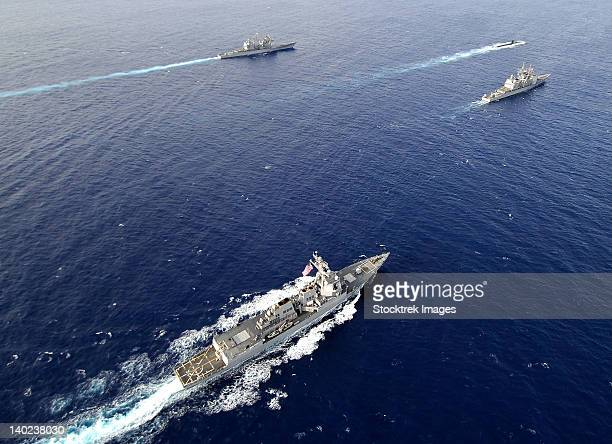 Aerial view of a naval fleet transiting the Pacific Ocean.
