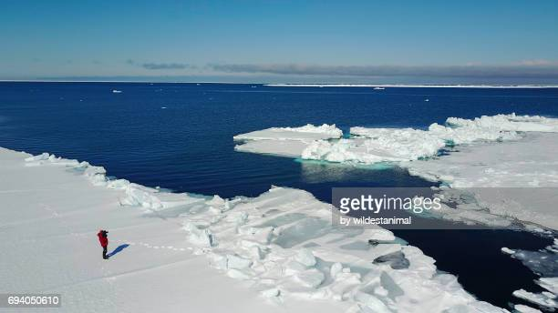 Aerial view of a photographer standing at the ice floe edge.