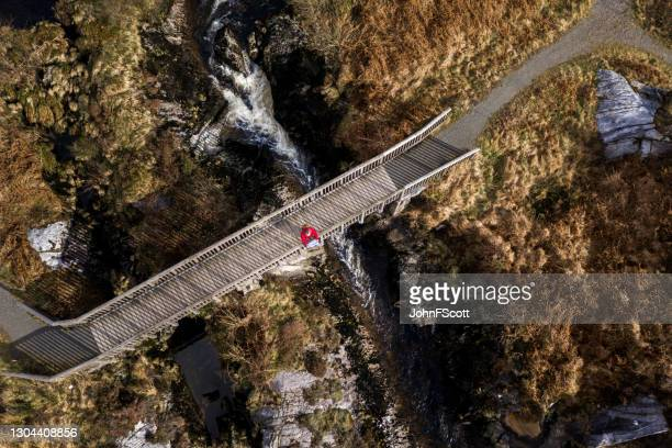 aerial view of a retired man on a footbridge - johnfscott stock pictures, royalty-free photos & images
