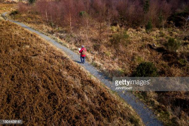 aerial view of a retired man walking on a footpath - johnfscott stock pictures, royalty-free photos & images