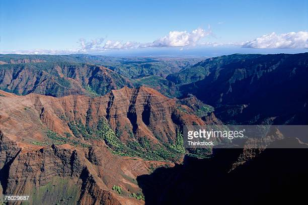 aerial view of a rocky mountain range with clouds lying above it. waimea canyon, kauai, hi - waimea valley stock photos and pictures