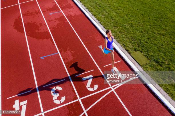 aerial view of a running young female athlete on a tartan track crossing finishing line - laufwettbewerb der frauen stock-fotos und bilder
