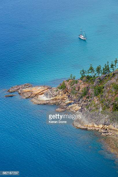 Aerial view of a sail boat approaching an island