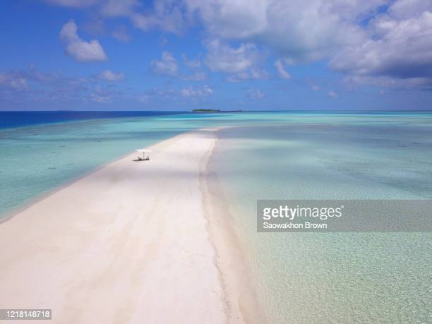 aerial view of a sandbank surrounded by turquoise water in maldives. soft waves breaking on it. - atoll stock pictures, royalty-free photos & images