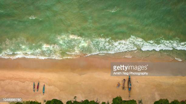Aerial view of a sandy beach with fisherman, their boats and beautiful clear sea water