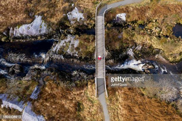 aerial view of a senior man using on a footbridge - johnfscott stock pictures, royalty-free photos & images