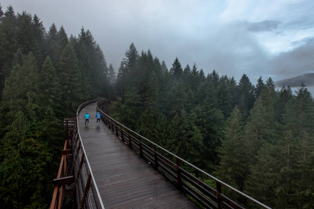 Aerial view of a senior women riding bicycles over an old trestle bridge in the rain