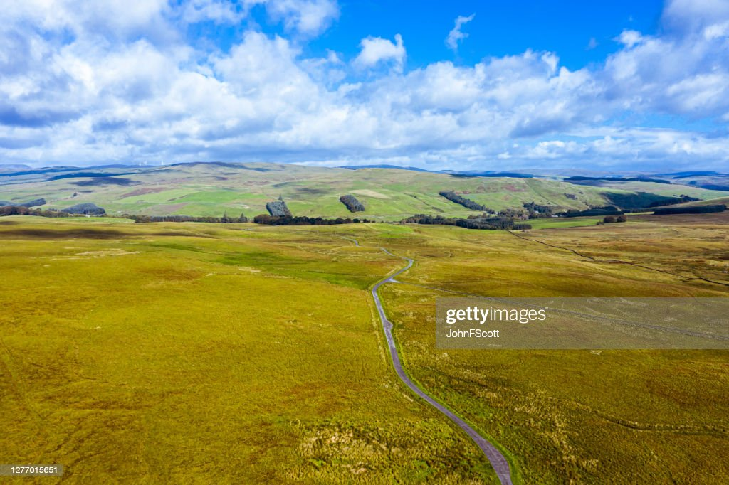 Aerial view of a single lane road running through remote open Scottish countryside : Stock Photo