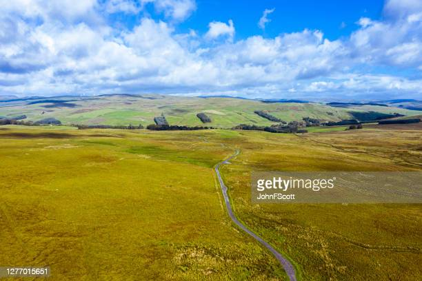 aerial view of a single lane road running through remote open scottish countryside - johnfscott stock pictures, royalty-free photos & images