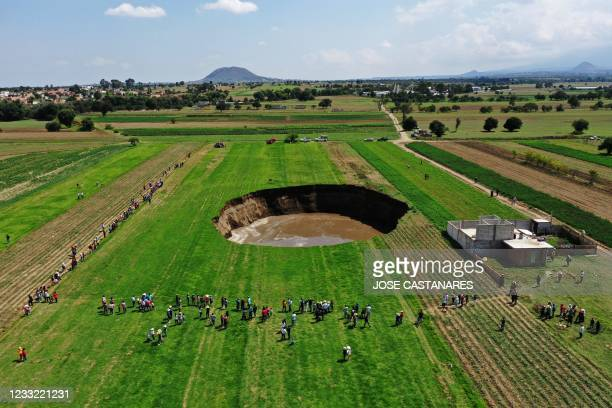 Aerial view of a sinkhole that was found by farmers in a field of crops in Santa Maria Zacatepec, state of Puebla, Mexico on May 30, 2021.