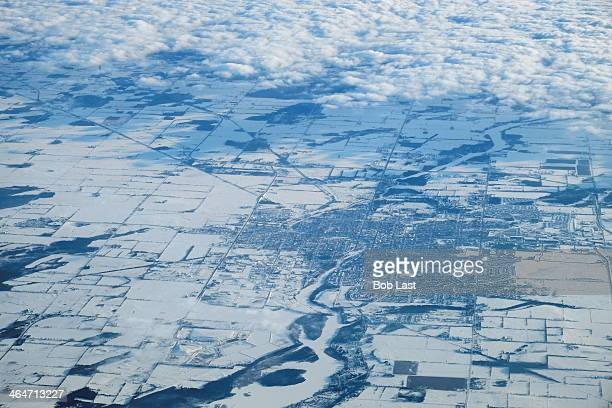 Aerial view of a small snow blanketed city north east of Toronto revealed as a cloud bank recedes
