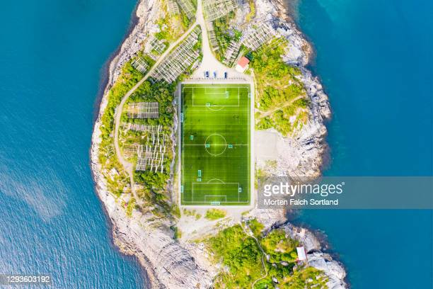 aerial view of a soccer field on an island in henningsvær, norway - football pitch stock pictures, royalty-free photos & images