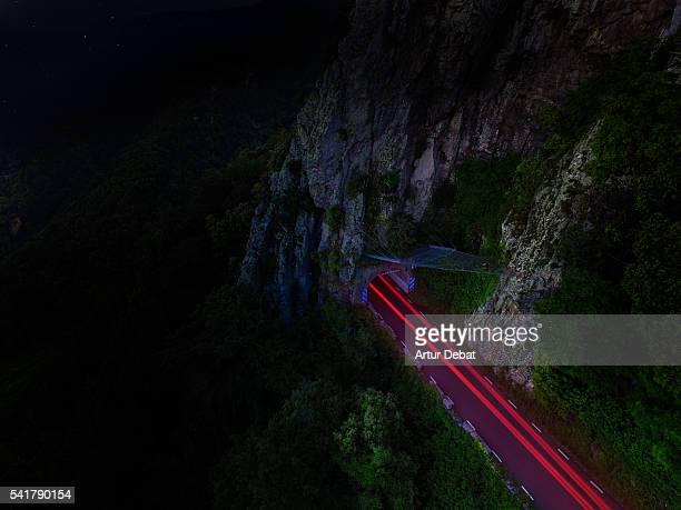 Aerial view of a stunning mountain road with wild place at night and red light trails of a car in the Montseny mountain range.