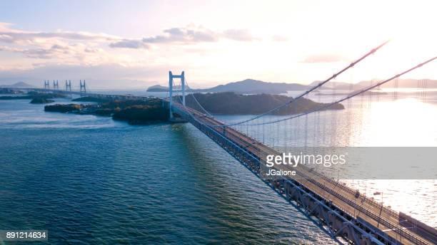 vista aérea de um pôr do sol sobre a ponte grande seto, japão - ponte - fotografias e filmes do acervo