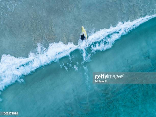 aerial view of a surfer girl - wassersport stock-fotos und bilder