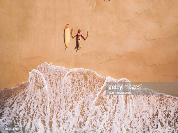 aerial view of a surfer girl resting on a beach - angel island stock photos and pictures