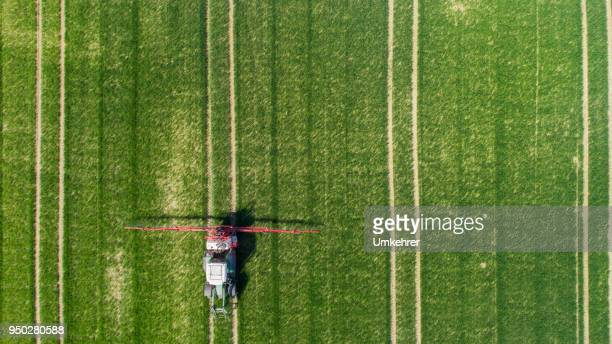 Aerial view of a tractor at green field