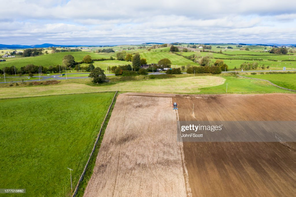 Aerial view of a tractor being used to pull a seed drill on a Scottish farm on a late summer day : Stock Photo