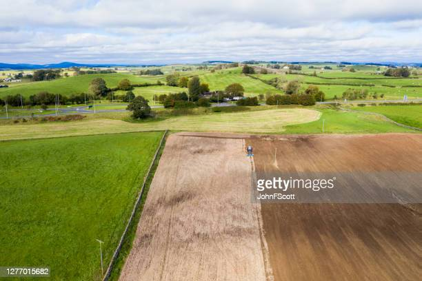 aerial view of a tractor being used to pull a seed drill on a scottish farm on a late summer day - johnfscott stock pictures, royalty-free photos & images