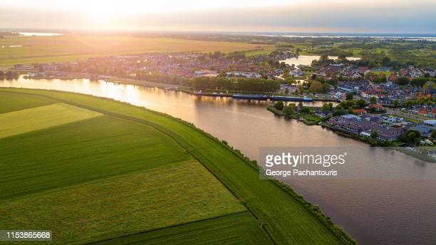 aerial view of a village next to the river and a field - netherlands stock pictures, royalty-free photos & images