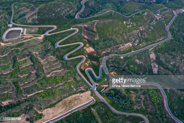 Aerial view of a winding road in red and blue on mountains at Yuquanshan forest park on June 29, 2020 in Taiyuan, Shanxi Province of China.