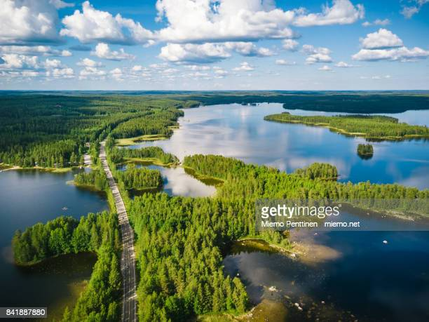 aerial view of a winding road passing through forests & lakes in finland on a summer day - finlandia fotografías e imágenes de stock