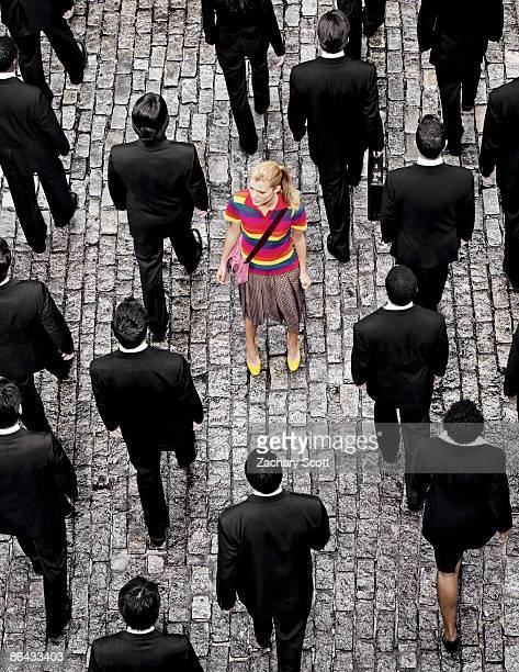 "aerial view of a woman ""standing out"" on a street - individualidad fotografías e imágenes de stock"
