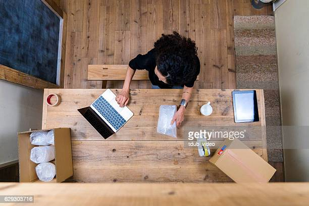 aerial view of a woman wrapping products - tdub_video stock pictures, royalty-free photos & images