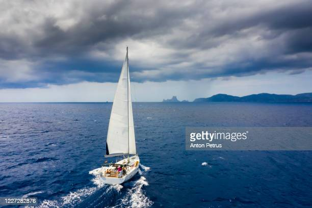 aerial view of a yacht in a storm with a dramatic sky - sailing stock pictures, royalty-free photos & images