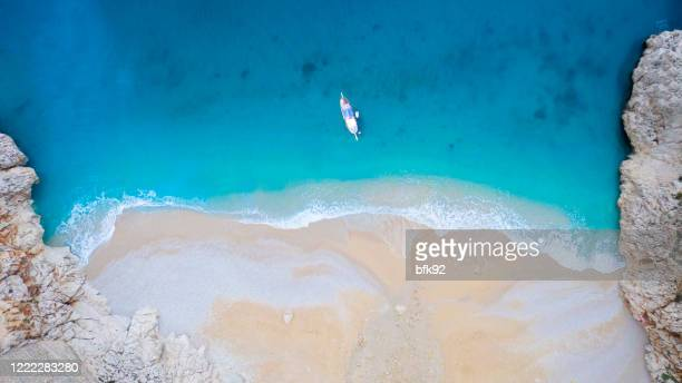 aerial view of a yacht stopped in a blue sea, kaputas, antalya, turkey. - kas stock pictures, royalty-free photos & images