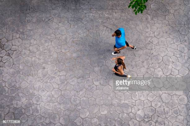 aerial view of a young couple running together - heterosexual couple stock pictures, royalty-free photos & images