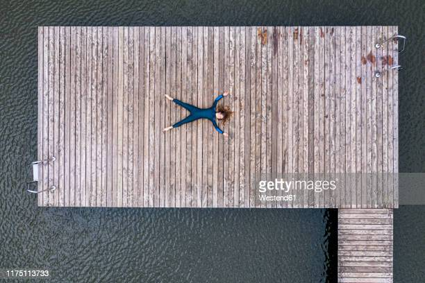 aerial view of a young female triathlete lying on jetty at a lake - jetty stock pictures, royalty-free photos & images