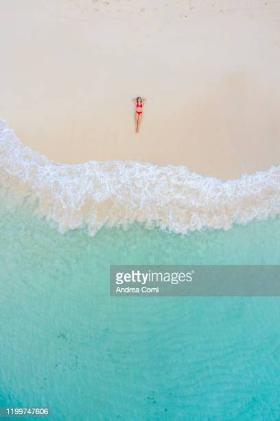 aerial view of a young woman lying down on a beach with turquoise sea. san blas islands, panama - lying down stock-fotos und bilder