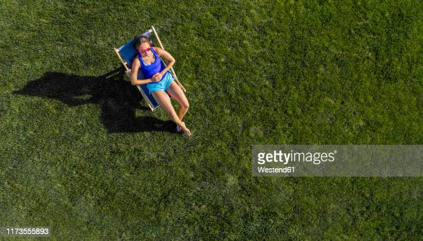 aerial view of a young woman sunbathing on lawn - cadeira dobrável - fotografias e filmes do acervo