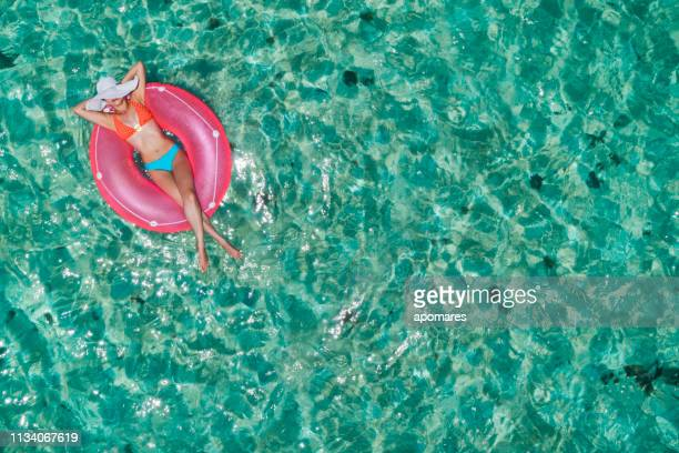 aerial view of a young women relaxing on inflatable ring in a tropical turquoise pristine beach - spring break stock pictures, royalty-free photos & images