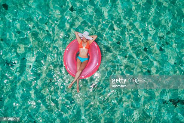 Aerial view of a young women relaxing on inflatable ring in a tropical turquoise pristine beach