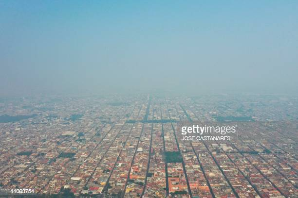 TOPSHOT Aerial view of air pollution in Puebla central Mexico on May 16 2019 A thick layer of smog envelops the city of Puebla abouth 100km southeast...