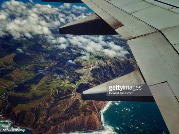 Aerial view of airplane wing flying over coastline