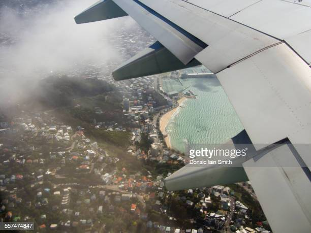 Aerial view of airplane wing flying over Wellington cityscape, Wellington, New Zealand