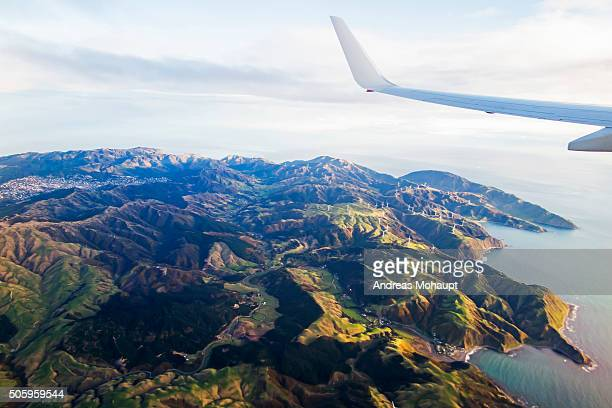 Aerial view of airplane wing flying over Wellington cityscape