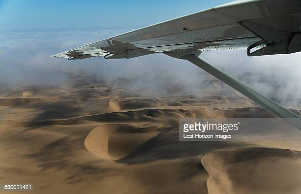 Aerial view of airplane wing over dunes, Namib Desert, Namibia