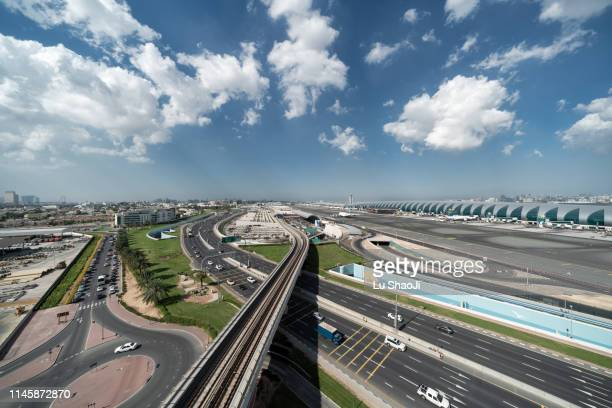 aerial view of airport terminal cloudy sky in dubai - dubai airport stock photos and pictures