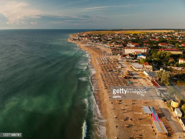 aerial view of amazing beach with umbrellas and turquoise sea at sunrise. black sea at vama veche, romania - romania stock pictures, royalty-free photos & images