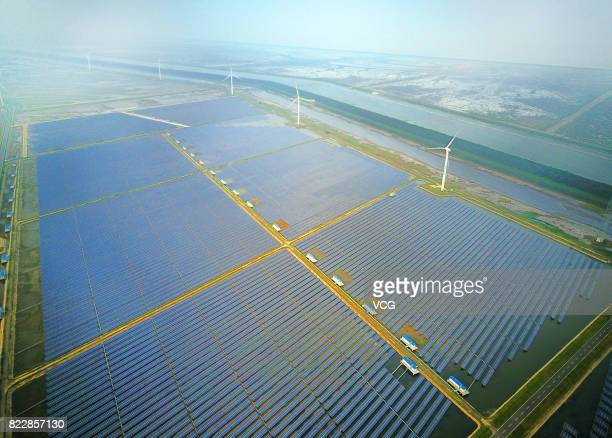 Aerial view of an industrial base consisting of wind turbines solar panels and fish ponds at tidal flats on July 25 2017 in Yancheng Jiangsu Province...