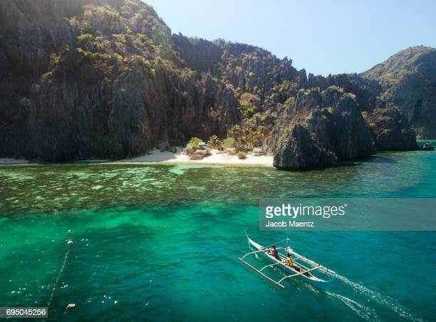 Aerial view of an outrigger boat and Tagbanua community on Coron Island, Palawan.