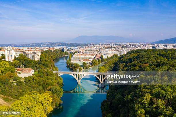 aerial view of arch bridge over river amidst trees in city - geneva switzerland stock pictures, royalty-free photos & images
