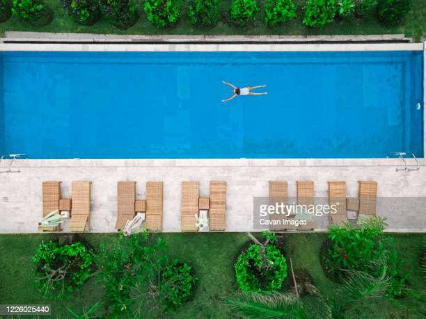 aerial view of attractive woman floating over water at resort - sun lounger stock pictures, royalty-free photos & images